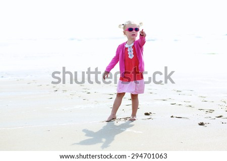 Cute active child wearing pink sunglasses playing and running on wide sandy beach. Happy little girl enjoying summer holidays on a sunny day. Family with young kids on vacation at the North Sea coast. - stock photo