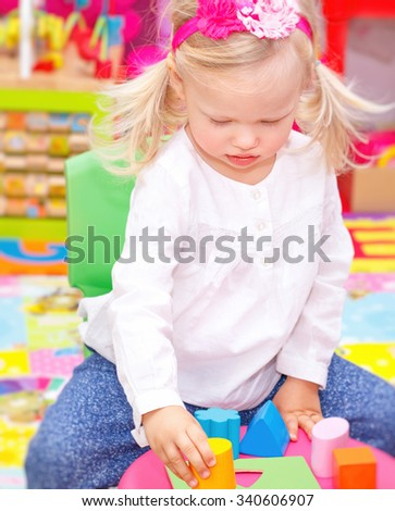 Cute adorable blond baby girl having fun in daycare, playing with colorful toys in playroom, happy healthy childhood - stock photo