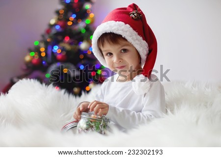 Cute adorable boy enjoying his candy at christmas time, holding jar with candies - stock photo