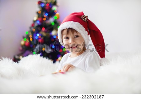 Cute adorable boy reading a book in front of the christmas tree, christmas time - stock photo