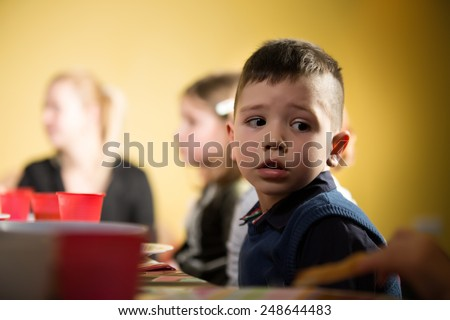 Cute adorable preschooler boy sitting in kindergarten looking confused.Sad child in kindergarten.Bored kid in preschool/kindergarten/nursery.Bored nervous boy at children birthday party - stock photo