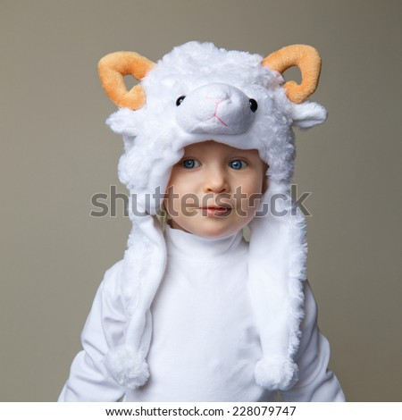 Cute adorable pretty Caucasian baby toddler with large blue eyes wearing a sheep hat hood with yellow horns on top and white shirt standing on a light background, New Year 2015 concept, studio - stock photo
