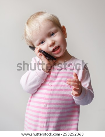 Cute adorable white  blond baby with blue eyes talking expressively emotionally over mobile cell phone with funny expression on her face, new technology future generation concept, on light background - stock photo