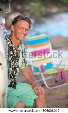 Cute adult Caucasian male outdoors sitting on beach - stock photo