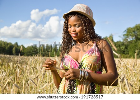 Cute African American woman smiling in a wheat field. - stock photo