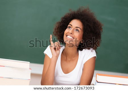 Cute African American woman with an inspired idea lifting her finger in excitement as she sits daydreaming in the classroom during college class - stock photo