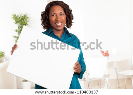 Cute African American woman with dark brown hair wearing a blue shirt. - stock photo