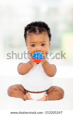 cute african baby girl biting her toy - stock photo