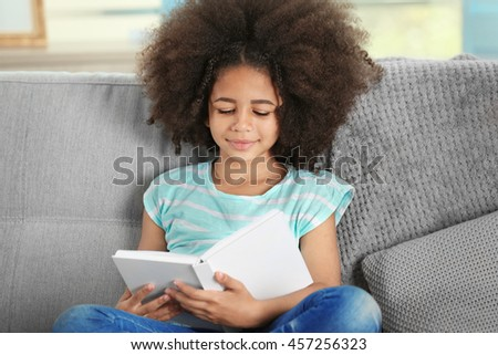 Cute African girl reading book on couch - stock photo
