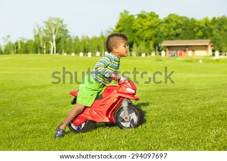 Cute afro boy on the red motorbike toy. - stock photo