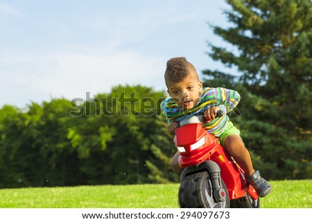 Cute afro boy plays and drives with the red motorbike toy on the sunny glade. - stock photo