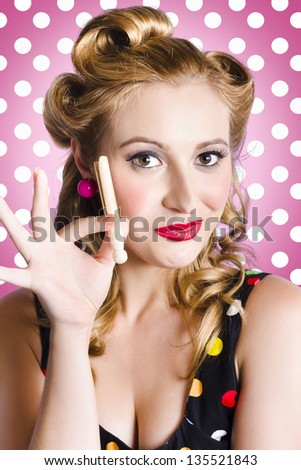 Cute amercian pinup girl with classic bright makeup and1950 hair curles holding laundry peg. Pink polka dot background - stock photo