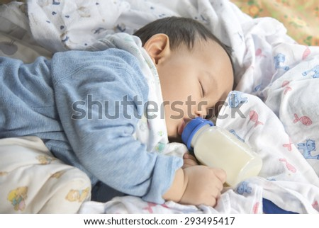 Cute and adorable Asian baby sleeping .Baby drinking milk from the bottle alone on the bed - stock photo