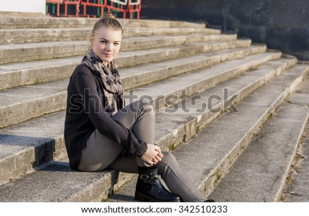 Cute and Beauty Caucasian Teenage Girl Posing Outdoors on Stairs. Horizontal Image Orientation - stock photo