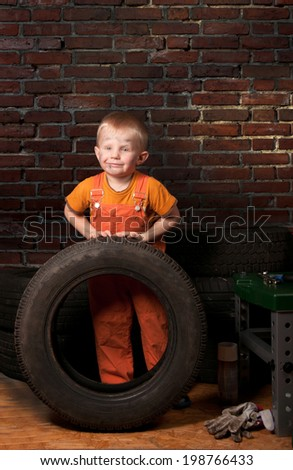 Cute and funny little mechanic with a tire  - stock photo