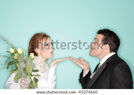 Cute and funny wedding couple blowing kisses - stock photo