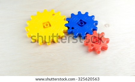 Cute and multicolor plastic gears or cogwheel on wooden surface. Concept of process and rotating mechanism. Slightly de-focused and close-up shot. Copy space. - stock photo