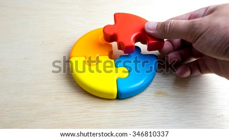 Cute and multicolor plastic pie chart or puzzle on wooden surface. Concept of process solution and teamwork collaboration. Slightly de-focused and close-up shot. Copy space. - stock photo