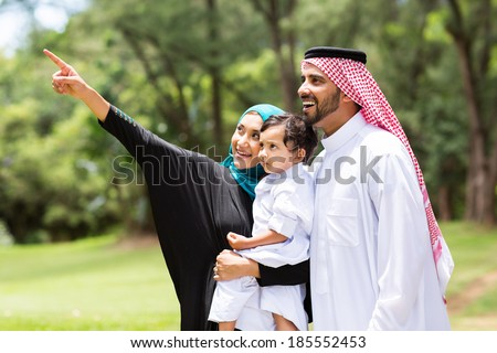 cute arabian family looking and pointing in the forest - stock photo