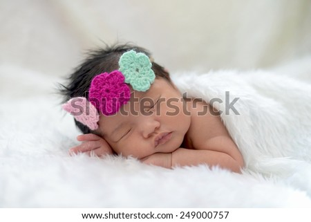 Cute asian baby girl sleeping on white cloth wearing colorful headband - stock photo