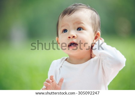 Cute asian baby laughing in garden (soft focus on the eyes) - stock photo