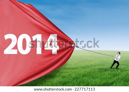Cute asian boy is pulling big banner of new year 2014 on the meadow - stock photo