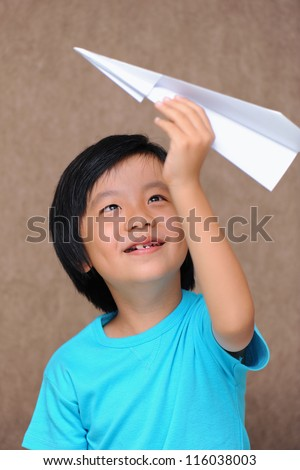 Cute Asian boy playing with paper plane - stock photo