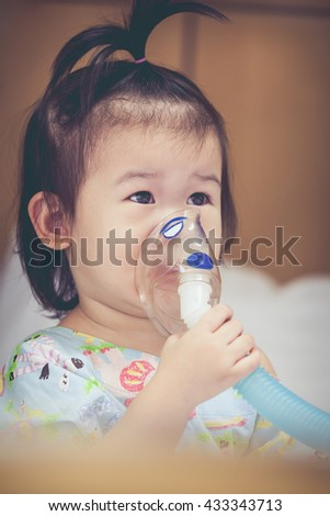Cute asian child holds a mask vapor inhaler for treatment of asthma on sickbed in hospital. Breathing through a steam nebulizer. Concept of inhalation therapy apparatus. Vintage tone. - stock photo