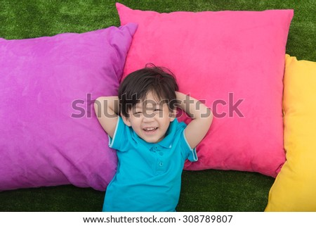 Cute asian child lying with colorful pilows on green grass - stock photo