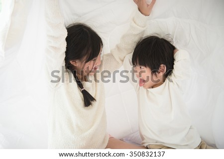 Cute asian children playing under blanket on white bed - stock photo