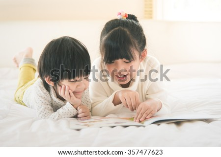 Cute asian children reading book on white bed,vintage filter - stock photo