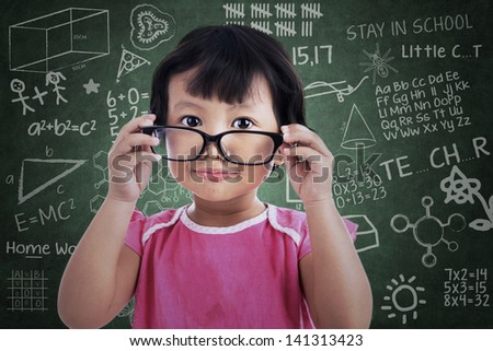 Cute asian girl holding glasses in classroom - stock photo