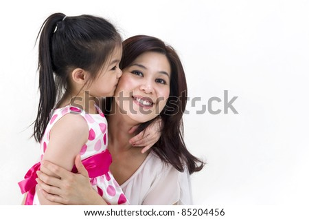 cute asian girl kissing her mother - stock photo