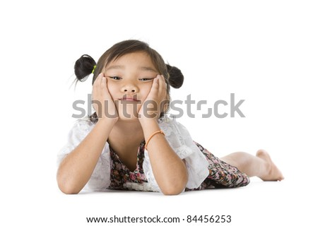 cute Asian girl laying on the floor, looking at the camera over white background - stock photo