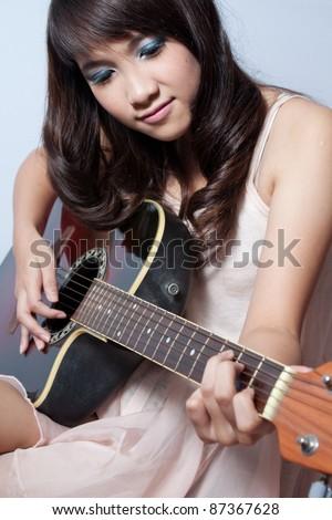 Cute asian girl playing guitar - stock photo