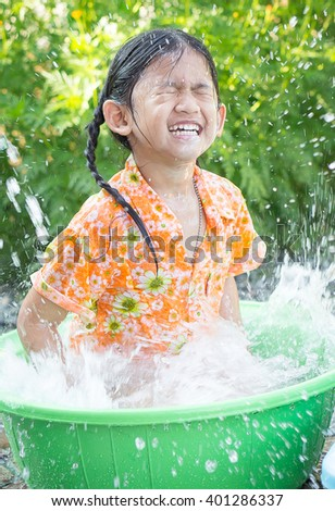 Cute Asian girl smiling when she playing with water in her little plastic basin on Songkran fastival Thailand.Songkran ceremony, Thai New Year. - stock photo
