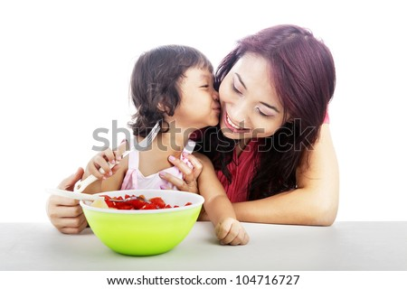 Cute asian little girl with fruit salad kissing her mother - stock photo