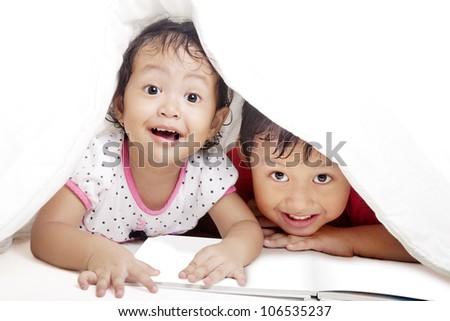 Cute asian siblings reading book under blanket. shot in studio - stock photo