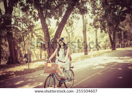 Cute Asian Thai girl in vintage clothing is riding a bicycle, in the sunny summer park in vintage color. - stock photo