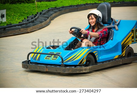 Cute Asian Thai girl is driving Go-kart car with speed in a playground racing track. Go kart is a popular leisure motor sports. - stock photo