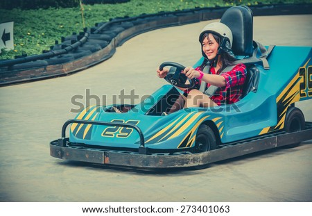 Cute Asian Thai girl is driving Go-kart car with speed in a playground racing track in vintage color. Go kart is a popular leisure motor sports. - stock photo