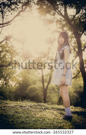 Cute Asian Thai girl is standing in the evening sunset through the wilderness in fairy tale style - stock photo