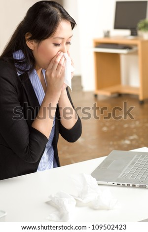Cute Asian woman in an office setting with a cold wearing a black suit and blue shirt - stock photo