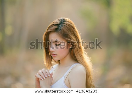 Cute asian woman in make a pray motion on blurred park view background - stock photo