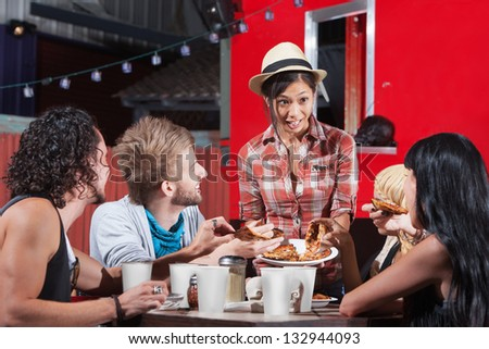 Cute Asian woman serving pizza to diners outside - stock photo