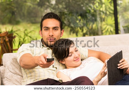 cute attractive couple cuddling in the sofa while watching tv and using tablet - stock photo
