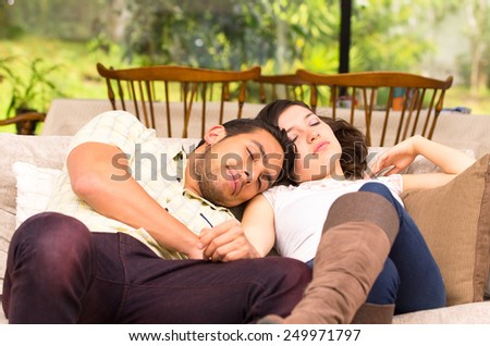cute attractive couple lying resting sleeping couple sofa - stock photo