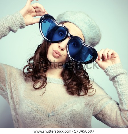Cute attractive fashion young girl posing at studio with funny big love glasses and gives kisses, toned - stock photo
