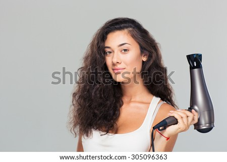 Cute attractive woman holding hairdryer over gray background. Looking at camera - stock photo