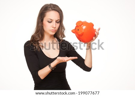 Cute attractive young brunette woman holding orange piggy bank. - stock photo